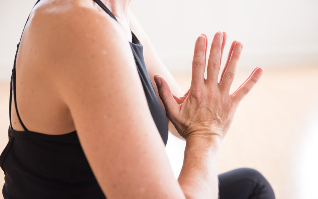 Woman doing yoga namaste pose at Elevate Yoga